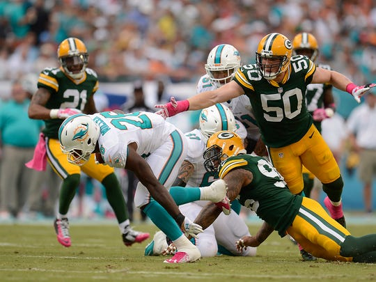 Packers linebacker A.J. Hawk (50) reaches for Dolphins