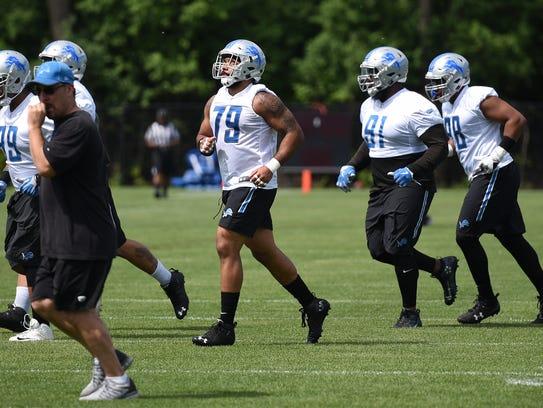 Detroit Lions defensive linemen head off the field