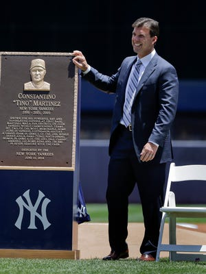 Former New York Yankees first baseman Tino Martinez stands next to a plaque that will be displayed at Yankee Stadium's Monument Park.