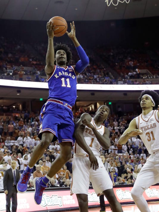 Kansas guard Josh Jackson (11) shoots over Texas defenders Andrew Jones (1) and Jarrett Allen (31) during the first half of an NCAA college basketball game, Saturday, Feb. 25, 2017, in Austin, Texas. (AP Photo/Eric Gay)