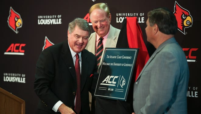 ACC commissioner John Swofford, from left, U of L president Frank Ramsey, and athletic director Tom Jurich unvile a plaque welcoming Louisville to the ACC Tuesday at the Schnellenberger Football Complex. June 1, 2014