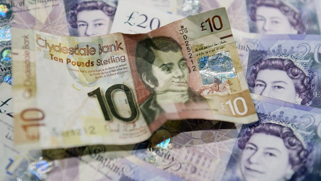 A Scottish 10 Pounds Sterling note lies amongst regular British Pound notes in Edinburgh, Scotland, on Sept. 11, 2014. Yes and NO camps in the Scottish referendum continue to debate whether Scotland can keep the pound as its own currency if it votes to become independent.