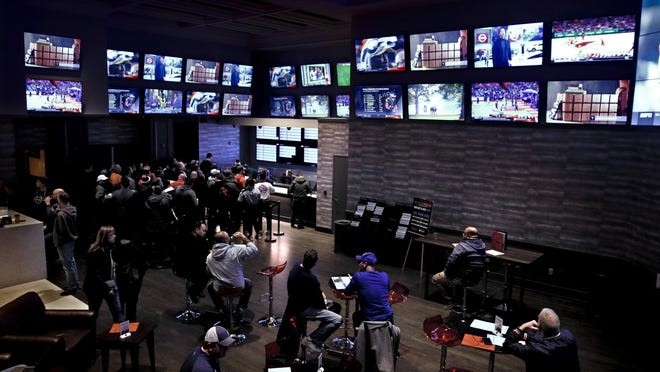An undated file photo shows some of the 102 screens to watch sports betting while enjoying food and drink inside Twin River's Sportsbook Bar and Grill.