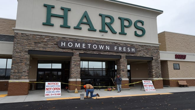 Workers put the finishing touches on the entrance of the new Harps store in Mountain Home on Tuesday. The store is set to open Wednesday morning, Dec. 10, 1014.