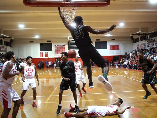 Lincoln's Dwight Wilson dunks the ball against Leon