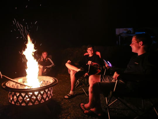 Seacrest Country Day School students Olivia Westervelt, 15, from left, Alexandre Chapelle, 15, and Thomas Richardson, 15, sit by the campfire Friday, Aug. 18, 2017, in Blue Ridge, Ga. A small group of students and staff from Seacrest made the trek to Georgia to witness the solar eclipse from the path of totality.