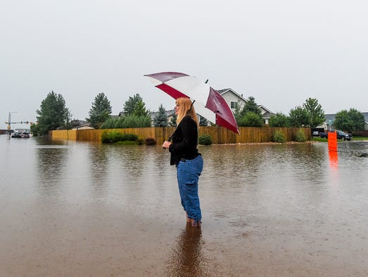 Ronda Gueswell stands on a flooded street in her neighborhood, Cornerstone, on Tuesday, July 29, 2014 in Windsor, CO. Windsor was hit by four inches of rain in 90 minutes.
