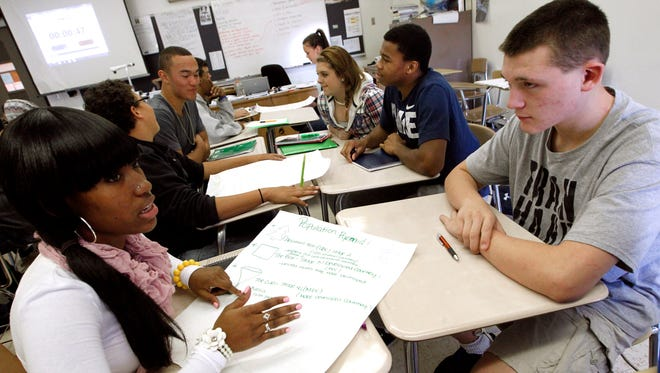 Hoover High School sophomore Keadra Foster, left, talks with Corbin Faidley, sophomore, during a classroom debate in his AP Human Geography class at Hoover High School.
