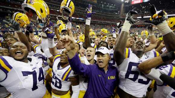 LSU coach Les Miles, center, is surrounded by his team as they celebrate beating Wisconsin in an NCAA college football game Saturday, Aug. 30, 2014, in Houston. LSU won 28-24.