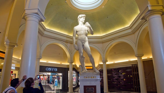 Guests take a photo of a life-sized replica of Michelangelo's David in the Appian Way Shops at Caesars Palace.