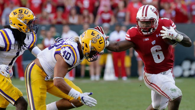 Wisconsin running back Corey Clement stiff-arms LSU linebacker Duke Riley during their game at Lambeau Field Sept. 3, 2016.