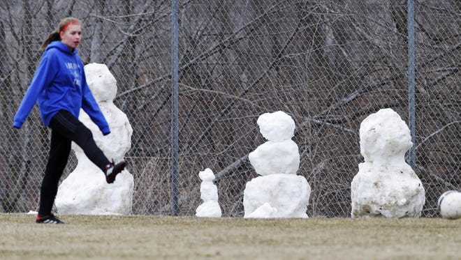 A Kettle Moraine Lutheran girls soccer player stretches her legs by a group of snowmen before an April 10 match in Plymouth.