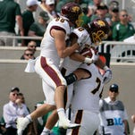Central Michigan's Anthony Rice, center, Jesse Kroll, left, and Derek Edwards celebrate Rice's touchdown reception against Michigan State during the second quarter of an NCAA college football game, Saturday, Sept. 26, 2015, in East Lansing, Mich.