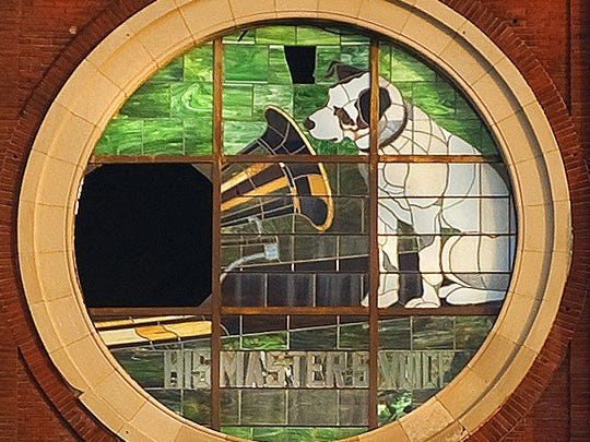 "This is one of the current ""Nipper"" windows on the former RCA Victor tower atop what is now the Victor Lofts housing complex on the Camden waterfront. One of the window's nine sections is missing. The trademark mascot first appeared on earlier windows 100 years ago when the Victor Talking Machine Co. built the tower to encase a company water tower."