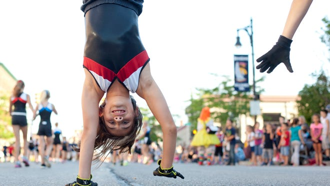 Jadzia Oronati-Phillips, 9, walks on her hands with members of the Flames Gymnastix during the Rotary International Day Parade in downtown Port Huron.