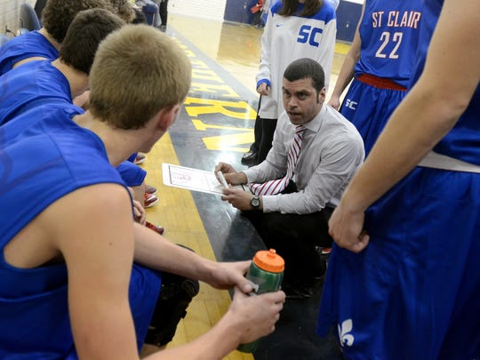 Saints' head coach, Shawn Sharrow, talks to his players during a timeout Friday, Dec 19 during a semifinal game of the Ed Peltz Holiday basketball tournament at Port Huron Northern.