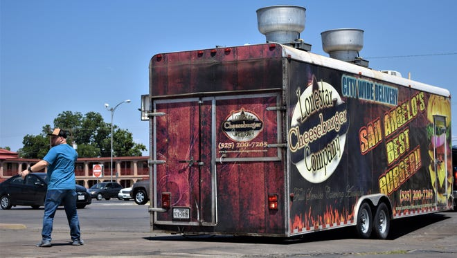 Tim Condon, owner of Lonestar Cheeseburger Company, supervises the moving of his food truck on July 25, 2018.