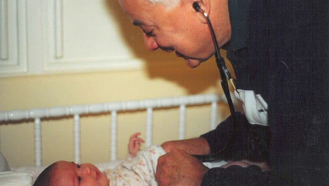 Dr. Alvaro Alandete, a Hanover pediatrician for more than 35  years, performs a checkup on a baby.