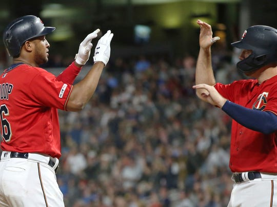 Minnesota Twins' Jonathan Schoop, left, and C.J. Cron celebrate Schoop's two-run home run off Texas Rangers' Jesse Biddle during the fifth inning of a baseball game Friday, July 5, 2019, in Minneapolis. (AP Photo/Jim Mone)