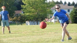Evening Sun Assistant Metro Editor Katy Petiford rolls a kickball against the Daily Record.