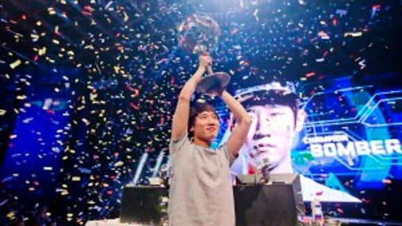 "Choi ""Bomber"" Ji Sung, raises the championship trophy after defeating Choi ""PoLt"" Seong Hun on July 13, 2014 (AP Photo/David Goldman)"