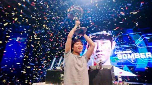 "Choi ""Bomber"" Ji Sung, raises the championship trophy after defeating Choi ""PoLt"" Seong Hun on July 13, 2014 (AP Photo/David Goldman)"