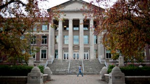 Student walks past the Hovde Hall of Administration building on the campus of Purdue University in West Lafayette, Ind.