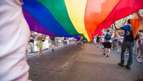 A woman runs under a giant rainbow flag  during the  WorldPride 2014 Parade in Toronto, Canada, June 29, 2014. (AFP PHOTO/ Geoff Robins/Getty Images)