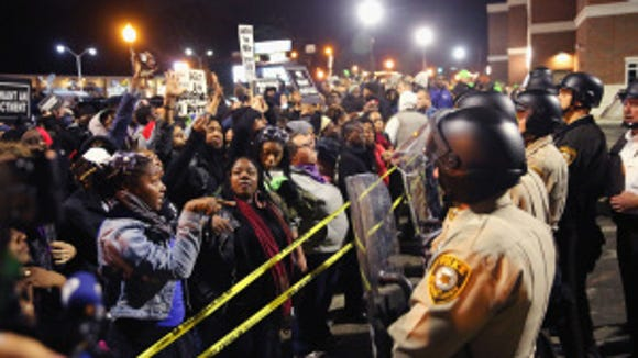 Demonstrators protest outside the Ferguson police department on October 11, 2014 in Ferguson, Missouri. (Photo by Scott Olson/Getty Images)