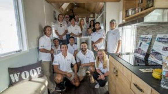 Portrait of the Tiny House team members inside their rEvolve House during the 2016 Tiny House Competition in Sacramento on October 13, 2016.  When the contest is over, the 238-square-foot solar-powered home will go to Operation Freedom Paws (OFP), a 501(c)3 nonprofit organization empowering military veterans and others with disabilities to restore their independence by teaming them up with a service dog. (Photo: Joanne H. Lee, Santa Clara University)