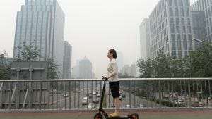 This picture taken on June 23, 2015 shows a woman riding an electric bike in smog covered Beijing.