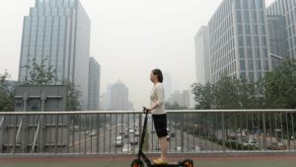 This picture taken on June 23, 2015 shows a woman riding an electric bike in smog covered Beijing.  (AFP PHOTOSTR/AFP/Getty Images)