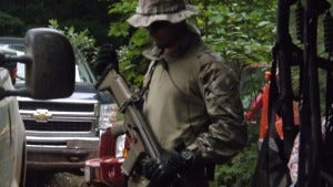 In this Sept. 17, 2013, photo, an armed, paramilitary-style guard hired by Gogebic Taconite patrols the site where the mining company hoped to build an open-pit iron mine in the Penokees of northern Wisconsin. The company pulled out of Wisconsin last month.