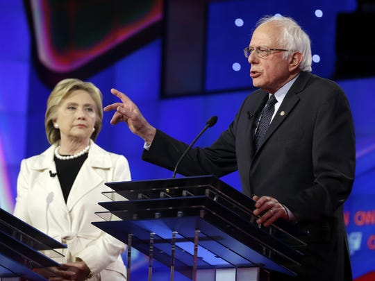 Vermont Sen. Bernie Sanders, right, speaks as former Secretary of State Hillary Clinton listens during the Democratic Presidential Primary Debate at the Brooklyn Navy Yard.