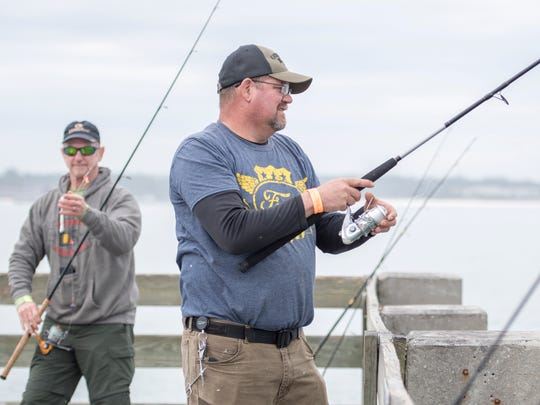 John Ahle, of Rochester, Minnesota,  left, and Richard Howell, of Knoxville, Tennessee, fish off the pier at Fort Pickens in Pensacola on Thursday, February 1, 2018.
