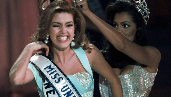 In this May 17, 1996, file photo, the new Miss Universe Alicia Machado of Venezuela reacts as she is crowned by the 1995 winner Chelsi Smith at the Miss Universe competition in Las Vegas. Machado still faces the threat of arrest in her native Venezuela as a result of alleged threats she made to a judge, according to a former lawyer who shares Donald Trump's revulsion at how his one-time client has been used by the Clinton campaign. (AP Photo/Eric Draper, File)