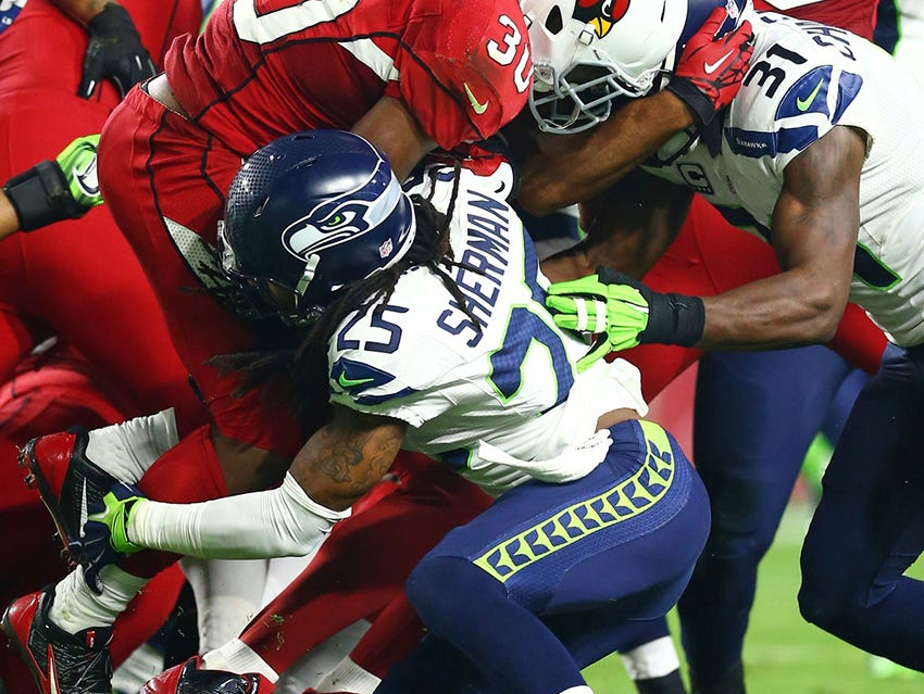 Richard Sherman of the Seattle Seahawks making a tackle leading with his shoulder.