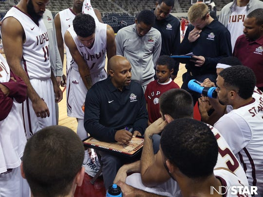 IUPUI basketball coach Jason Gardner gathers his team during a timeout in an exhibition at the Indiana State Fairgrounds Coliseum.