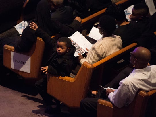 Family members gather as a memorial service is held