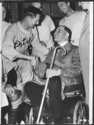 Walter O. Briggs congratulates his Detroit Tigers, starting with manager Del Baker in Cleveland on Sept. 28, 1940. The Tigers held off the Indians to win the AL pennant by one game.