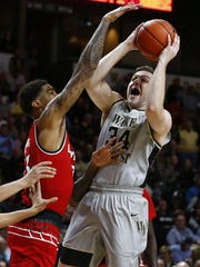 Wake Forest Demon Deacons forward Austin Arians (34) goes up for a shot against the Louisville Cardinals in the first half at Lawrence Joel Veterans Memorial Coliseum.