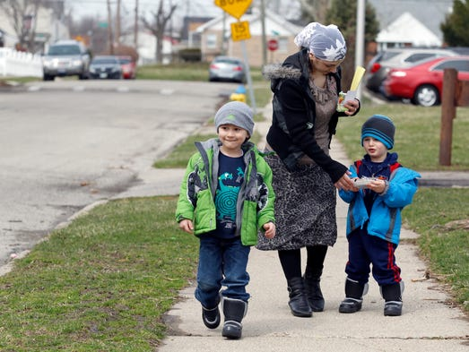 Nayla Kilich, a Turkish refugee from Russia walks in the Old North Dayton neighborhood with her son, Jon, 3, left, and nephew Asker, 2, after picking them up from day care. Kilich said she came to the United States in 2006 and has trained to be a phlebotomist and is currently volunteering at Miami Valley Hospital in Dayton. Dayton has become home to about 530 Turk refugee families since 2005.