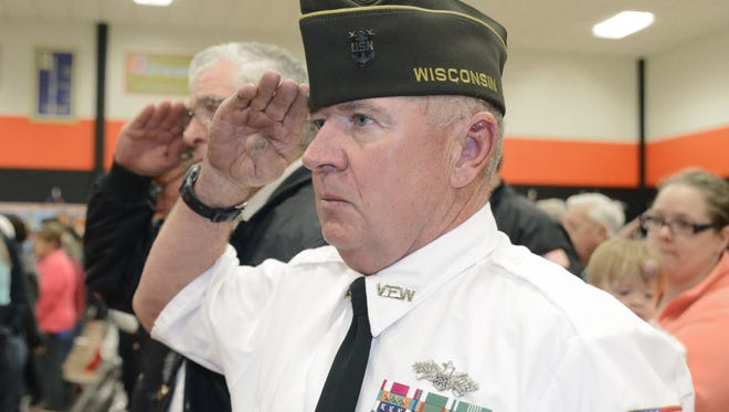 Brian Benzinger salutes to honor the fallen soldiers during a Veterans Day event at O.H. Schultz Elementary School on Wednesday,  Nov. 11, 2015, in Mishicot. Benzinger served in the U.S. Navy Seabees from 1977-2014.