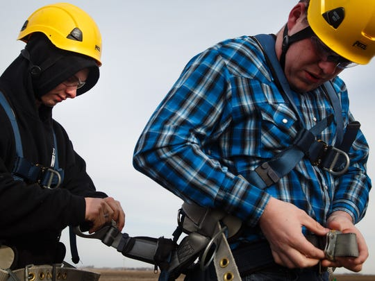 Alex Edwards,19 of Indianola, left, helps Chris Jackson, 21 of Bonderant, put on his harness before climbing a wind turbine in Dana on Friday, April 20, 2018. Students from Des Moines Area Community College climbed the turbine as part of their class to become technicians