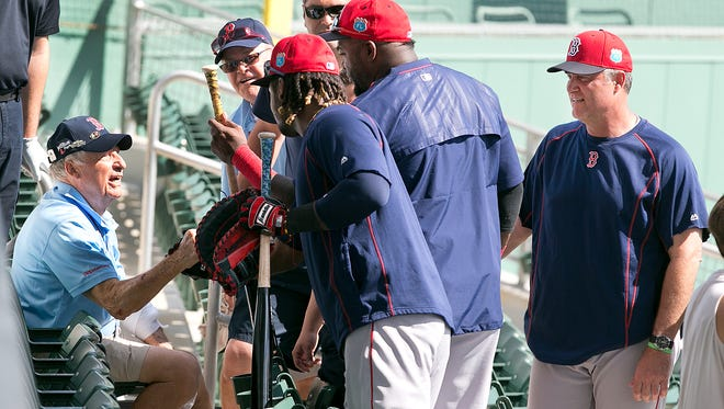 """JetBlue Park usher Merton """"Buzz"""" Dunham, 80,talks with Red Sox players Hanley Ramirez, David Ortiz and manager John Farrell after being struck by a ball during batting practice on Monday. Ramirez and Ortiz gave him presents, including a bat."""