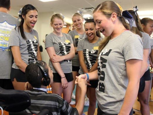 Chrissy Ferraro, 18, of Westville creates a secret handshake with Joffre Surdez, 14, a resident of Children's Specialized Hospital, as the Union County football team and cheerleaders visit Children's Specialized Hospital as part of the charity festivities of Snapple Bowl XXI in Mountainside, NJ Monday July 14, 2014.  Staff photo Tanya Breen