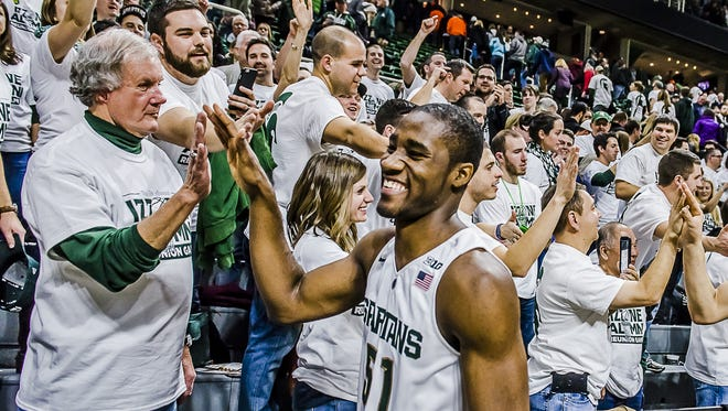 MSU walk-on Greg Roy high-fives fans after the Spartans' win over Illinois Thursday night. Roy made his MSU debut Thursday, playing the final 20 seconds.