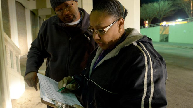 Fred McKinnie and Evelyn Henning document one of the homeless men sleeping at the Carl Perkins Civic Center on Tuesday night during the Jackson-Madison County annual homeless count.
