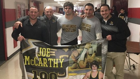 Senior Joe McCarthy (center) earned his 100th career victory with a major decision in the tournament final of the Gary Vittorio Holiday Classic.