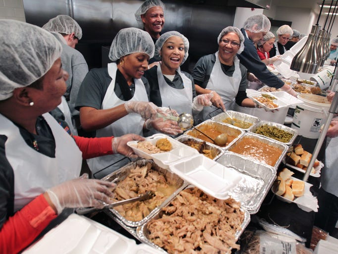 Volunteers, left to right Cherie Coleman, LaTasha Nixon, Teres Foster, and Tanya Goggans prepare some of the 4,000 meals at the annual Mozel Sanders Thanksgiving dinner event at Butler University's Atherton Building on Thursday, Nov. 28, 2013. About 2,000 volunteers helped cook, dish out and deliver the meals around Indianapolis. Altogether, 15,000 pounds of turkey, 10,000 pounds of dressing, 80,000 dinner rolls, 1,200 gallons of gravy, plus apple crisp and green beans were distributed.